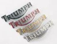 """This is a gold decal on the side of the gas tank. Measures approx 6"""". Reads -----Triumph---"""